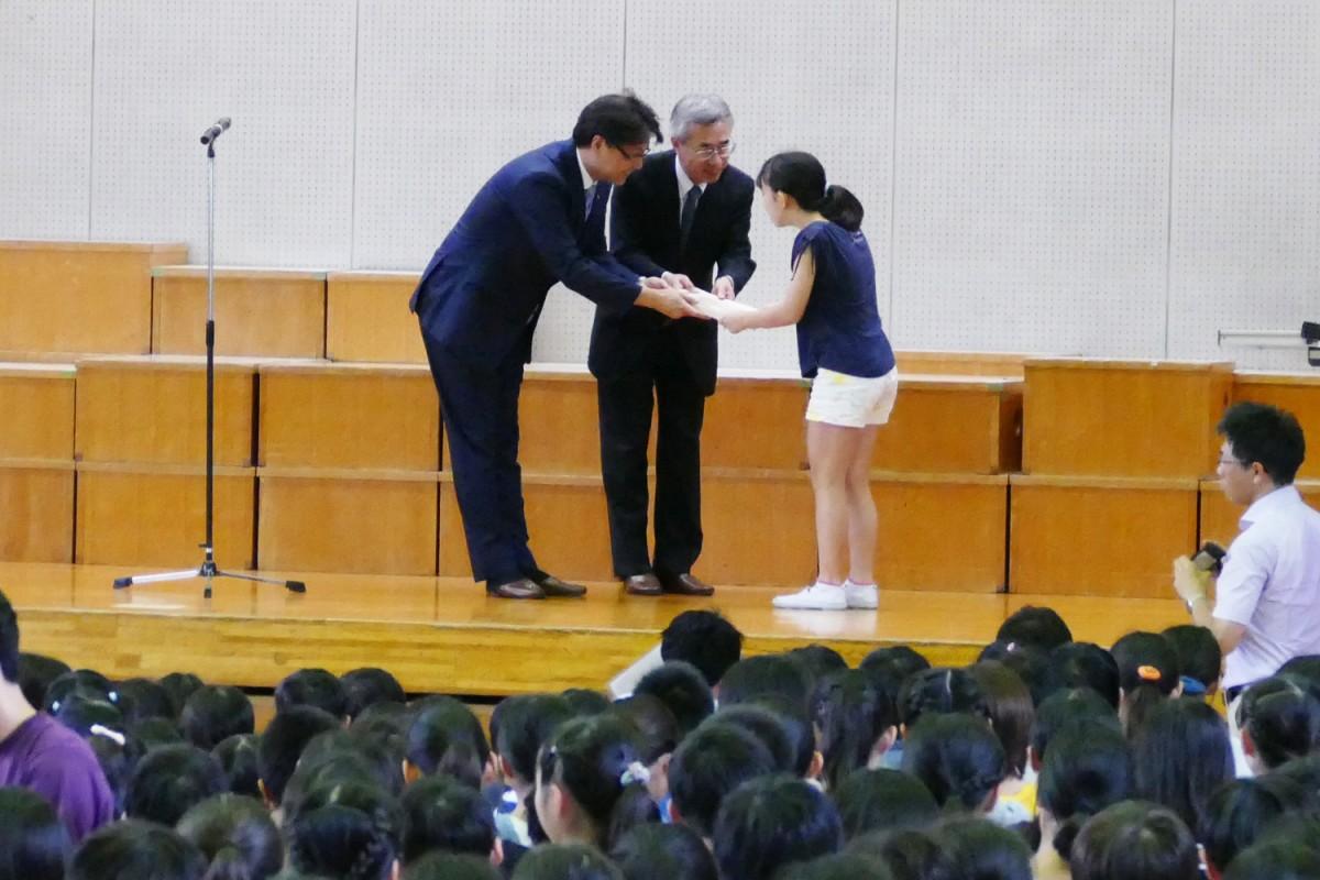 全校児童の前で代表者に贈呈