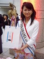 「横浜フランス月間・2005」の紙袋を手渡す横浜観光親善大使の小堀愛さん